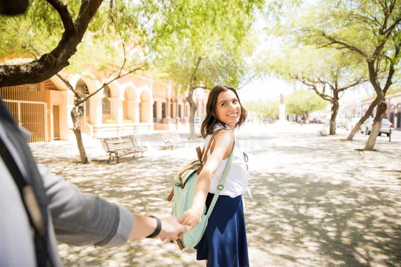 愉快的少妇握一个人的手在街道上的 免版税库存照片