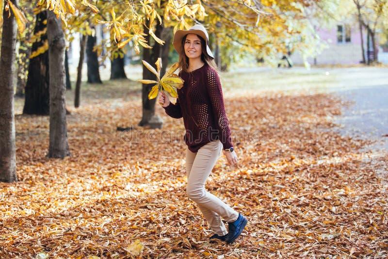 愉快的少妇有乐趣时间在秋天户外 快乐微笑的女孩跳跃的跑在秋天森林里 免版税库存照片