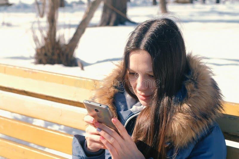 愉快的少妇浅黑肤色的男人在冬天城市公园键入在她的电话的一则消息坐长凳在晴天 侧视图 免版税库存图片