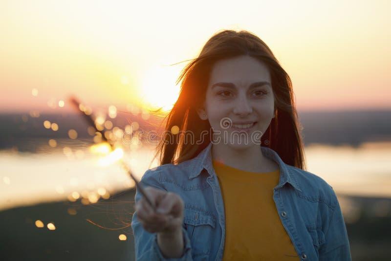 愉快的少妇画象有闪烁发光物的在手中在夏天晚上 库存图片