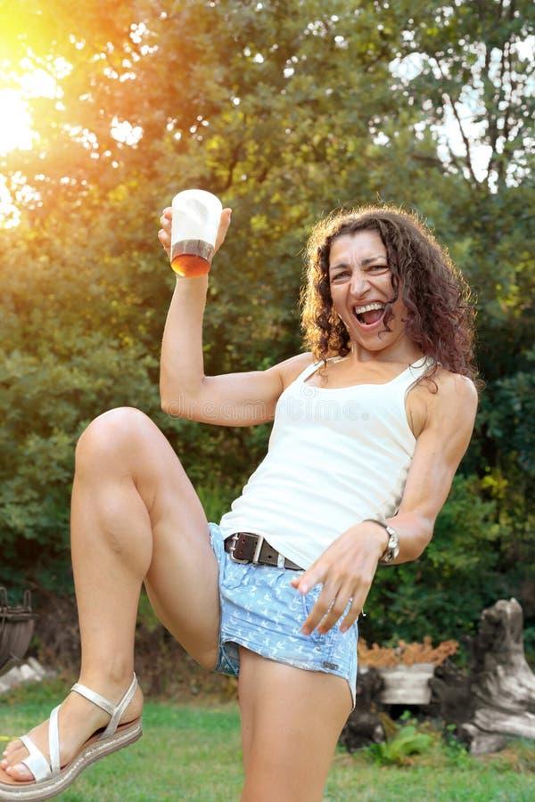愉快的少妇获得乐趣在夏天党饮用的鸡尾酒在日落 免版税库存照片