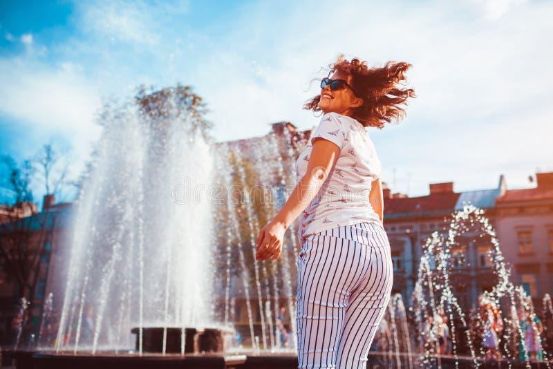 愉快的少妇赛跑和跳舞由喷泉在夏天街道上 免版税库存照片