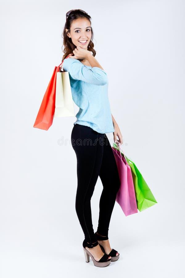 愉快的少妇运载的购物袋画象  免版税库存照片