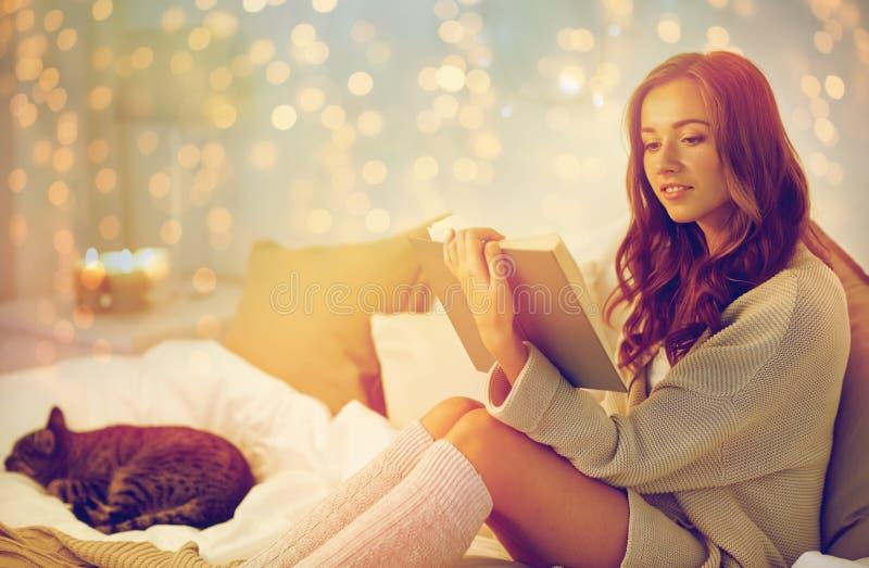 愉快的少妇阅读书在床上在家 免版税图库摄影