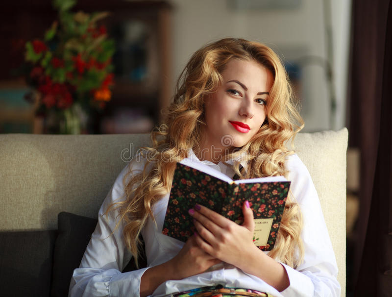 愉快的少妇阅读书在家 免版税图库摄影