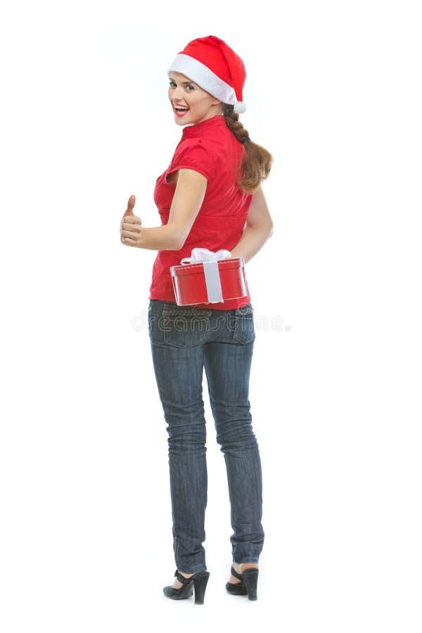愉快的少妇隐藏的圣诞节礼物配件箱 免版税库存照片