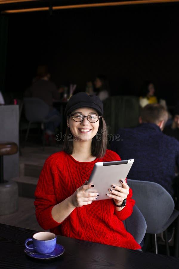 愉快的少妇饮用的咖啡/茶和使用片剂计算机在咖啡店 免版税图库摄影