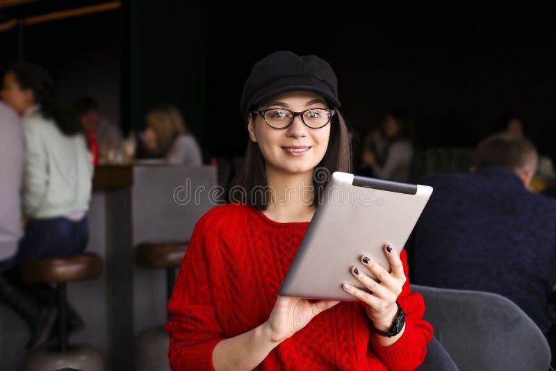愉快的少妇饮用的咖啡/茶和使用片剂计算机在咖啡店 库存图片