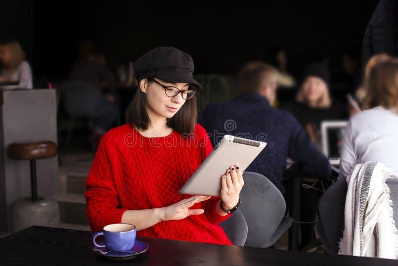 愉快的少妇饮用的咖啡/茶和使用片剂计算机在咖啡店 库存照片