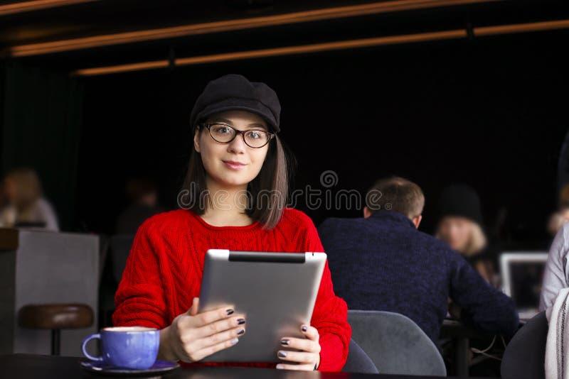 愉快的少妇饮用的咖啡/茶和使用片剂计算机在咖啡店 免版税库存图片