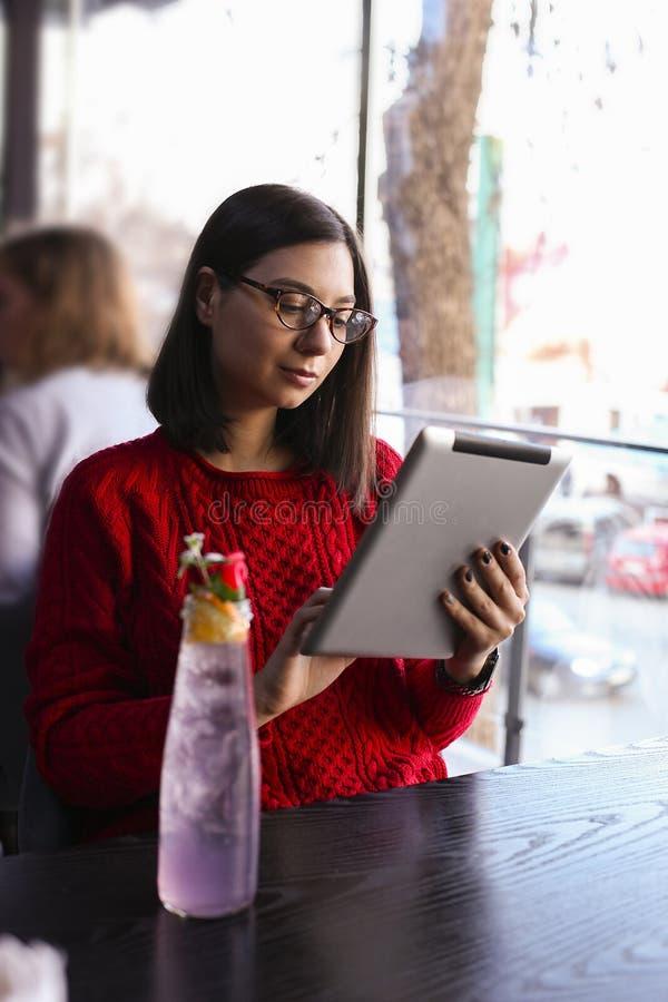 愉快的少妇饮用的柠檬水/冰了茶和使用片剂计算机在咖啡店 图库摄影