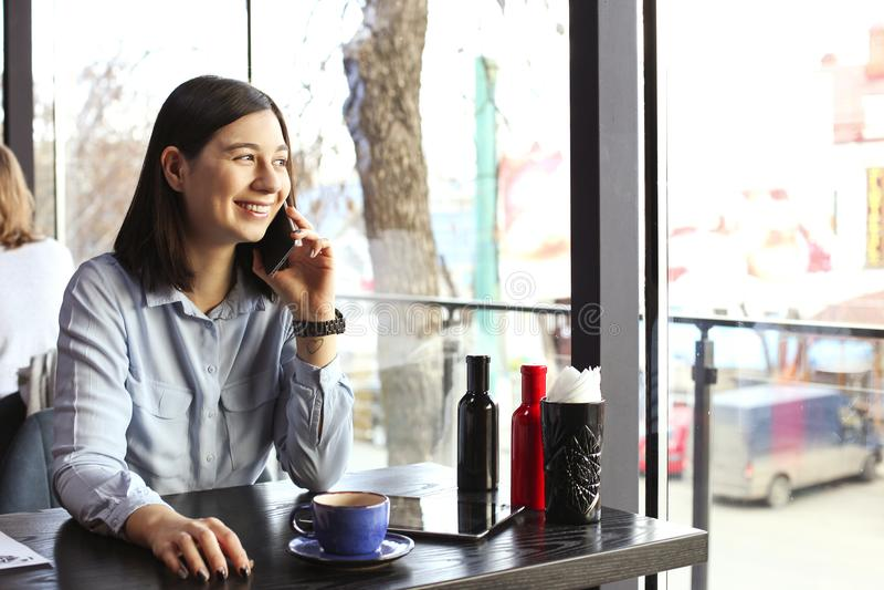 愉快的少妇饮用的热奶咖啡,拿铁, macchiato,茶,使用片剂计算机和谈话在咖啡店/ba的电话 库存照片