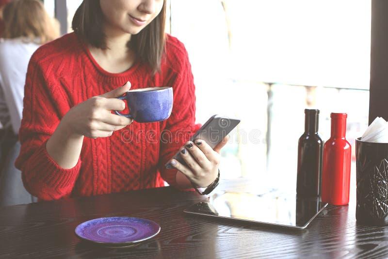 愉快的少妇饮用的热奶咖啡,拿铁, macchiato,茶,使用片剂计算机和谈话在咖啡店/ba的电话 库存图片