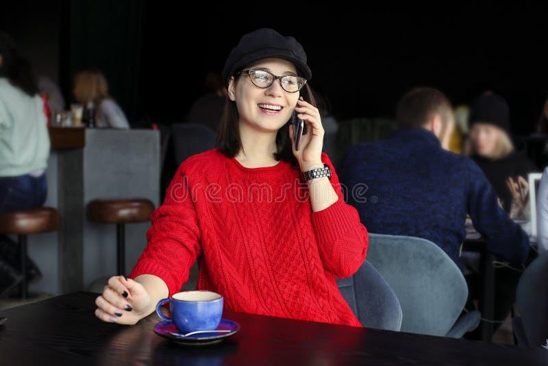 愉快的少妇饮用的热奶咖啡,拿铁, macchiato,茶,使用片剂计算机和谈话在咖啡店/ba的电话 免版税库存照片