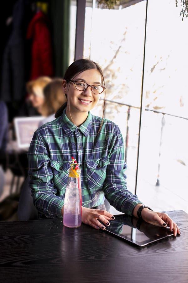 愉快的少妇饮用的热奶咖啡,拿铁, macchiato,茶,使用片剂计算机和谈话在咖啡店/ba的电话 免版税库存图片