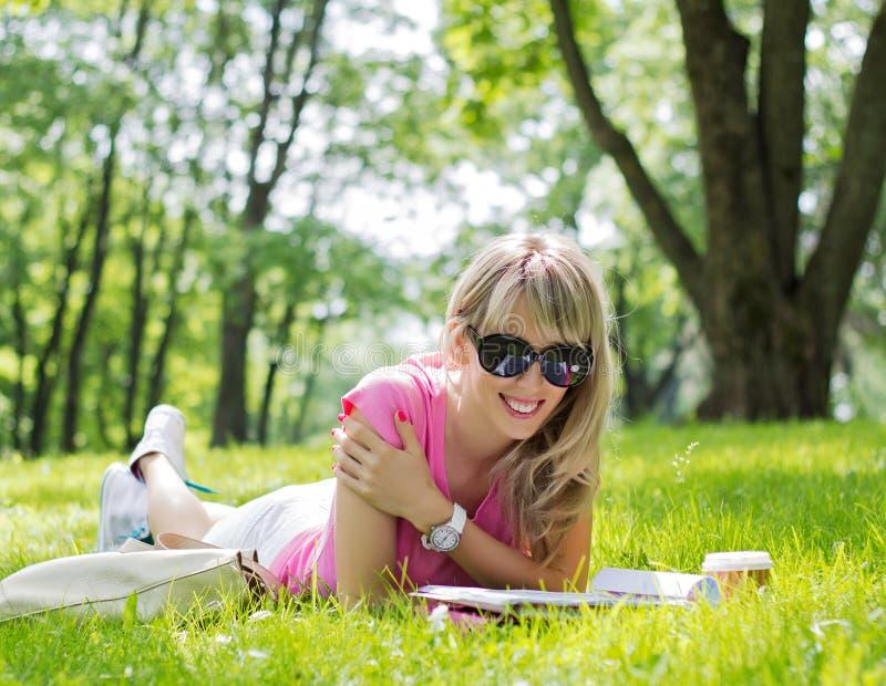 愉快的少妇读书杂志在公园 免版税库存照片