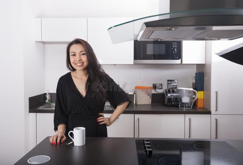 愉快的少妇画象有咖啡杯的在厨房里 免版税库存图片