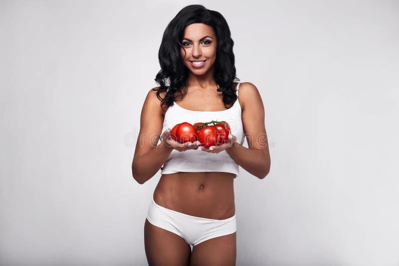 愉快的少妇画象用蕃茄 免版税库存图片