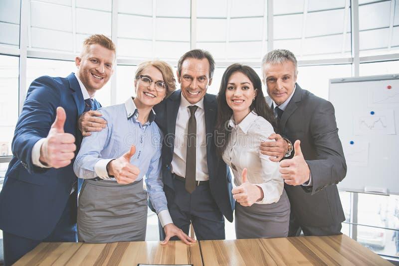 愉快的工作的队在办公室站立 免版税图库摄影