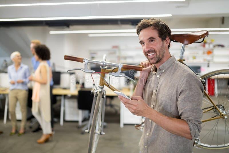 愉快的工友商人运载的自行车在现代办公室 免版税库存照片