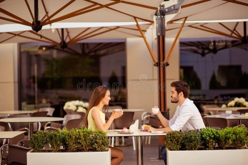 愉快的已婚夫妇在蜂蜜月亮,有早午餐在与现代内部,与绿色好的pla的轻的夏天大阳台的美味的咖啡馆 免版税库存照片