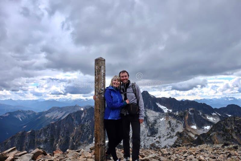 愉快的已婚夫妇户外在山顶面微笑和拥抱在风暴天空下 库存图片