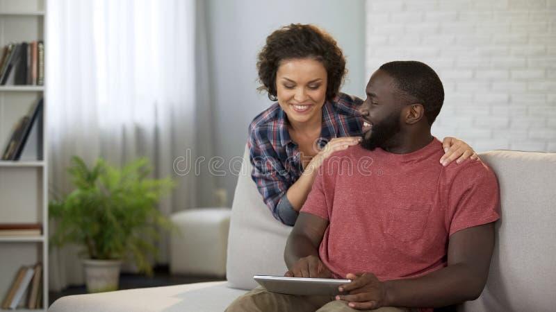 愉快的已婚夫妇计划旅行海外,在网上选择旅馆和航空公司 免版税图库摄影
