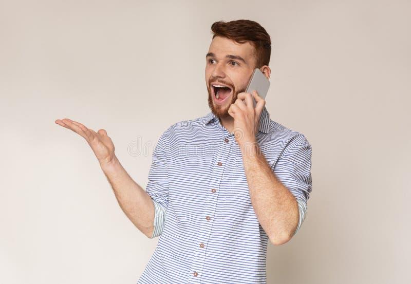 愉快的帅哥听见喜讯谈在电话 库存照片