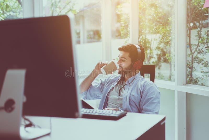愉快的帅哥用胡子饮用的咖啡和在网上听到音乐在现代办公室,正面认为,放松时间 免版税库存图片