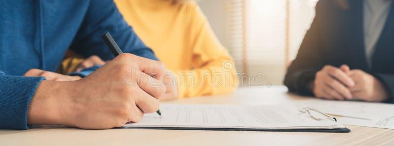 愉快的年轻亚洲夫妇和地产商代理 签署有些文件的快乐的年轻人,当坐在书桌与他的妻子一起时 库存照片