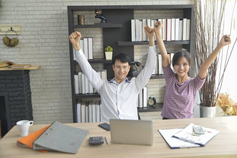 愉快的年轻亚裔商人和女孩举了庆祝的手 库存图片