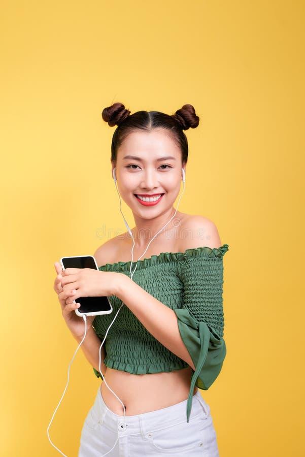 愉快的年轻亚裔妇女五颜六色的演播室画象有earphon的 免版税库存图片