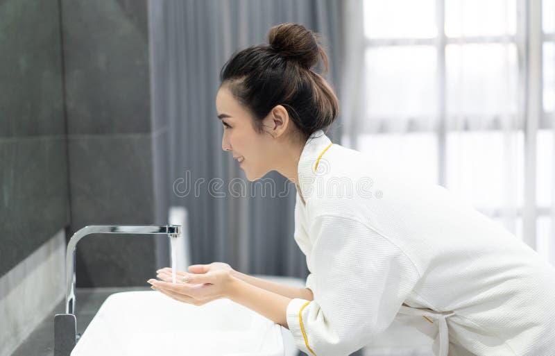 愉快的年轻亚裔妇女画象,当洗她的面孔和看在卫生间时反映 自然皮肤护理和人概念 免版税库存图片
