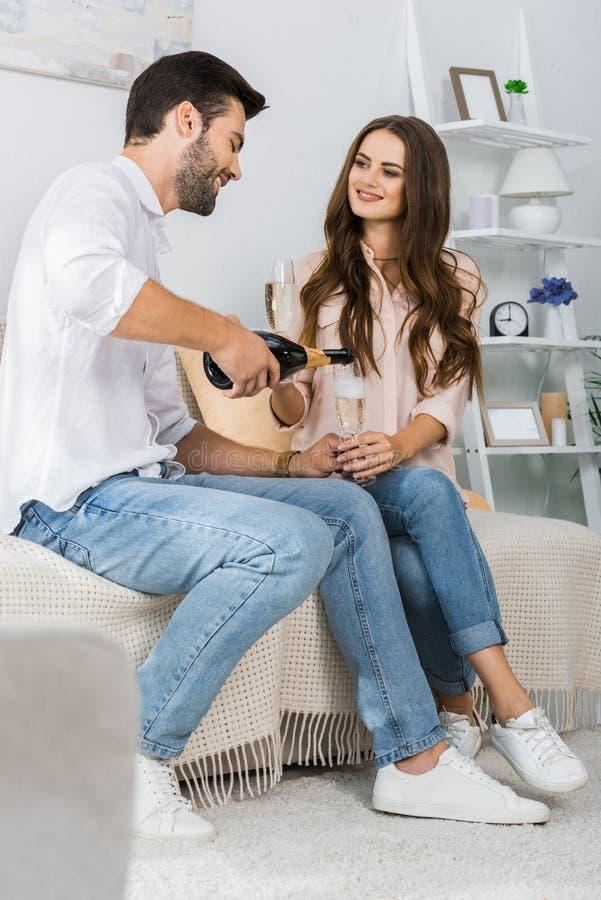 愉快的年轻人倾吐的香槟到玻璃里,当坐有女朋友的时长沙发 库存照片