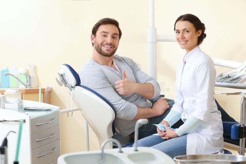 愉快的年轻人和女性牙医在治疗以后在诊所 库存照片