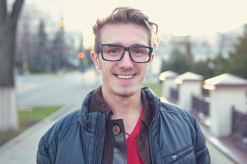 愉快的年轻人在街道上穿破 免版税图库摄影