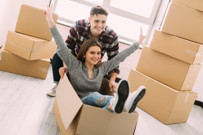 愉快的年轻人微笑夫妇获得与纸板箱的乐趣在新房移动的天 库存图片