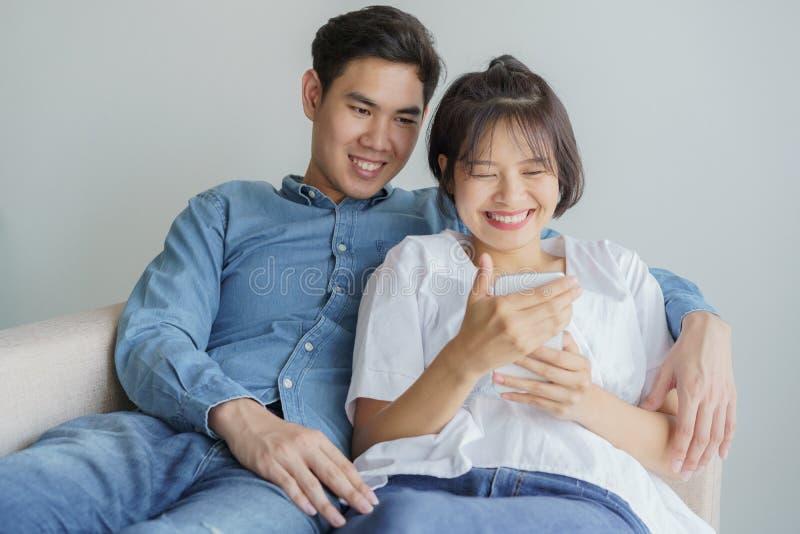 愉快的年轻人爱亚洲夫妇在家坐长沙发,看手机,年轻亚裔人民使用智能手机 图库摄影