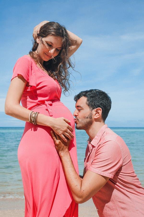 愉快的年轻人父亲kising的女孩` s胃 怀孕新的生活 库存图片