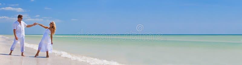 愉快的年轻人结合跳舞握在海滩全景的手 库存图片