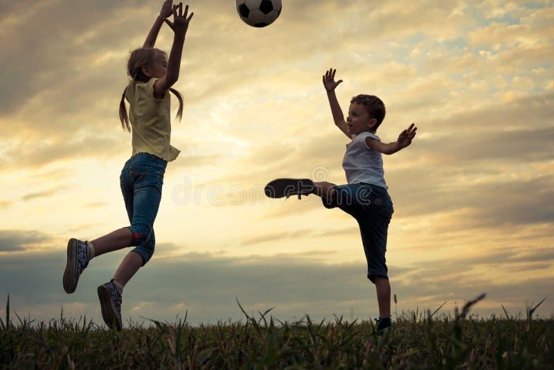 愉快的年轻使用在与socce的领域的小男孩和女孩 免版税库存照片