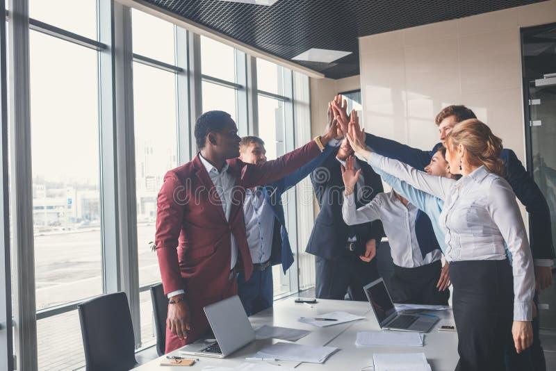 愉快的年轻做上流五的businesswomans和businessmans在办公室 免版税库存照片