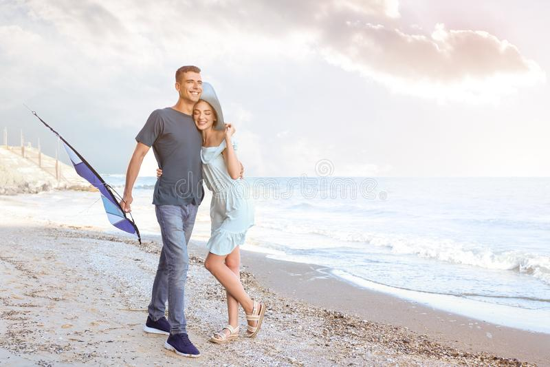 愉快的年轻加上在海附近的风筝 免版税库存照片