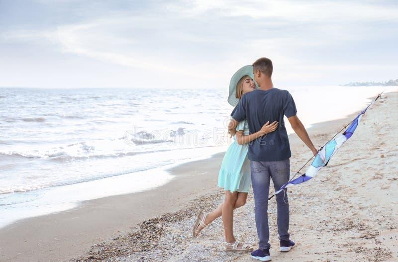 愉快的年轻加上在海附近的风筝 图库摄影