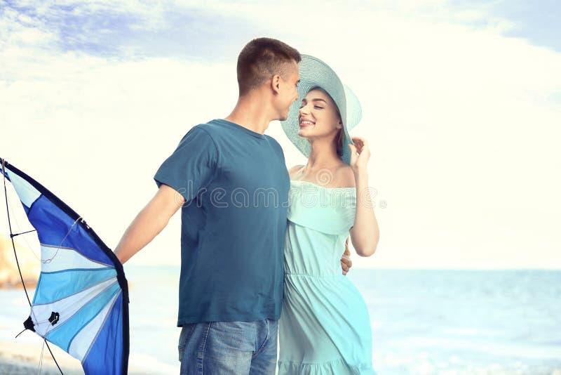 愉快的年轻加上在海附近的风筝 免版税库存图片