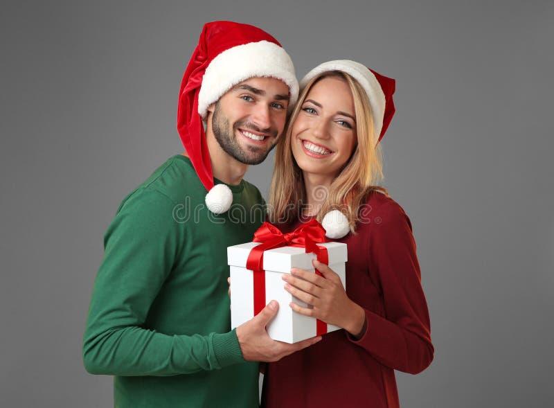 愉快的年轻加上在灰色背景的圣诞节礼物 库存图片