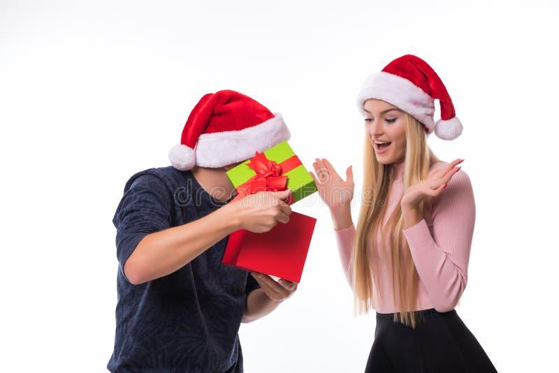 愉快的年轻加上在白色背景的圣诞节礼物 妇女圣诞前夕的人开放礼物 免版税库存照片