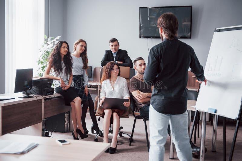愉快的年轻同事谈论在会议在创造性的办公室 免版税库存图片