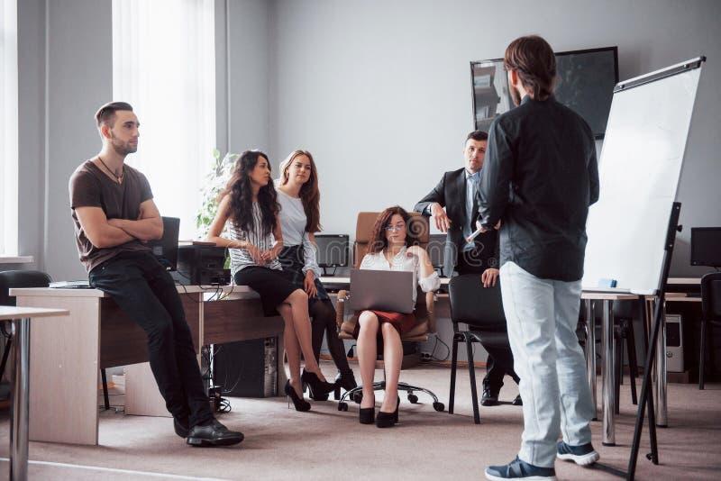 愉快的年轻同事谈论在会议在创造性的办公室 库存图片