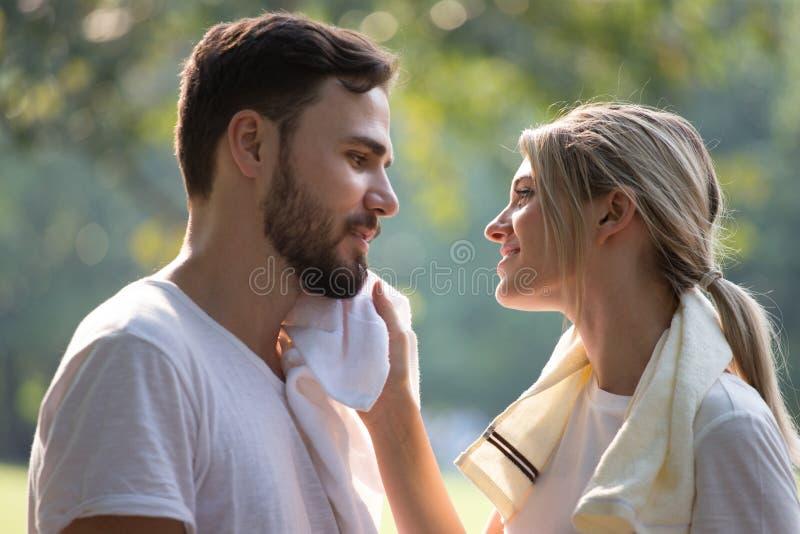 愉快的年轻在一起放松在公园的运动服的夫妇爱恋的健身在早晨时间 以后休假的体育人 免版税库存照片